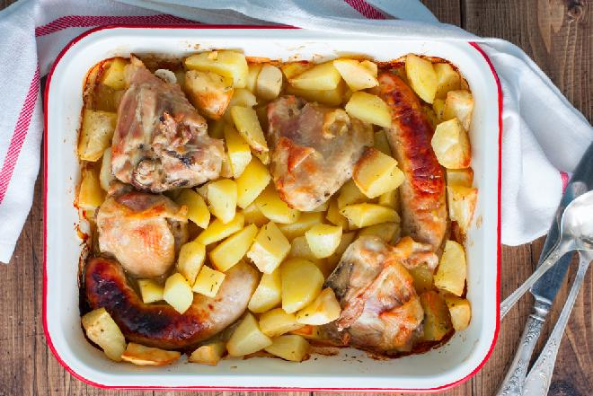 Ziemniaki, udka kurczaka i biała kiełbasa z piekarnika: pyszny obiad dla całej rodziny